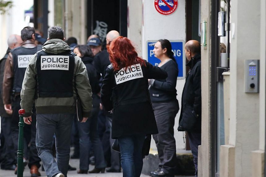 Policemen arrive to investigate at the entrance of the headquarters of French daily newspaper Liberation, on Nov 18, 2013, in Paris, after a gunman opened fire in the hall of the building, injuring one person said to be a photographer. -- PHOTO: AFP