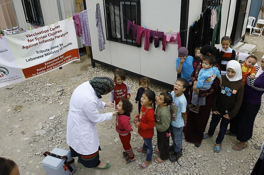 Displaced Syrian displaced line up to receive a vaccination against polio at one of the Syrian refugee camps in the southern port city of Sidon, Lebanon on Thursday, Nov 7, 2013. Turkey on Monday, Nov 18, 2013, announced a mass vaccination campa
