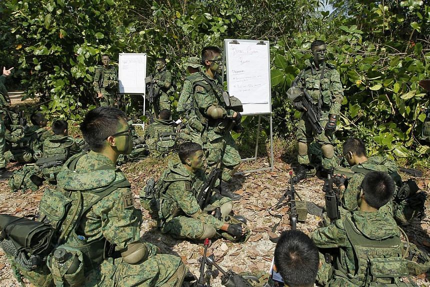 Full-time National Service (NS) specialist cadets from Lima Company, Specialist Cadet School, share lessons before a training exercise near Pasir Laba Camp, on July 1, 2013. -- PHOTO: ST FILE