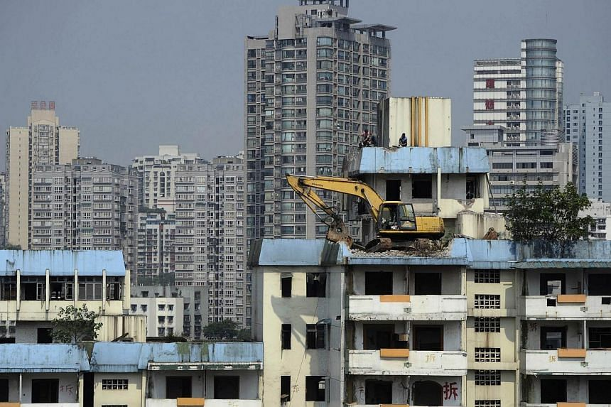An excavator works to demolish an old building from a rooftop next to a new residential area in Chongqing Municipality, Sept 16, 2013. China's home prices hit fresh record highs in October, underlining the challenge facing the government just a few d