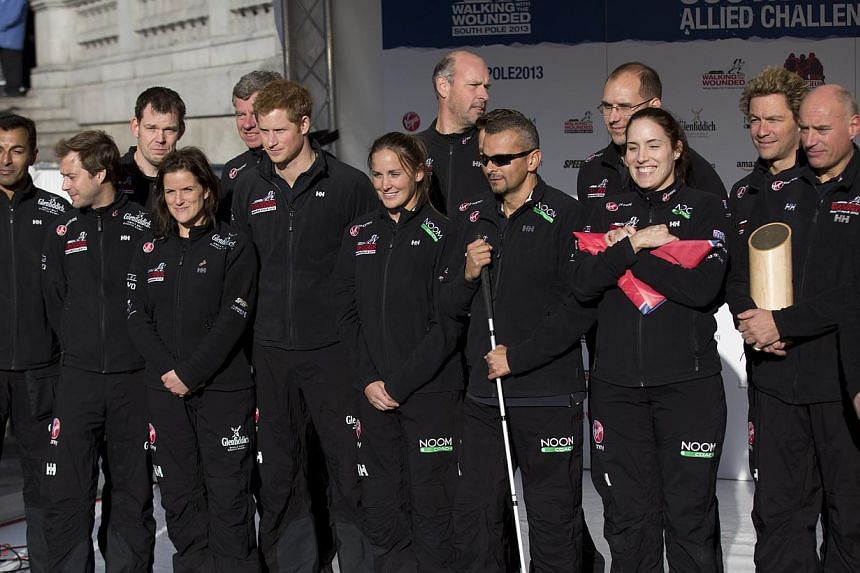 Britain's Prince Harry, sixth left, poses for a group photograph on stage with other people including actor Dominic West, fourth right, who will take part in the Walking With The Wounded South Pole Allied Challenge during its departure event in Trafa