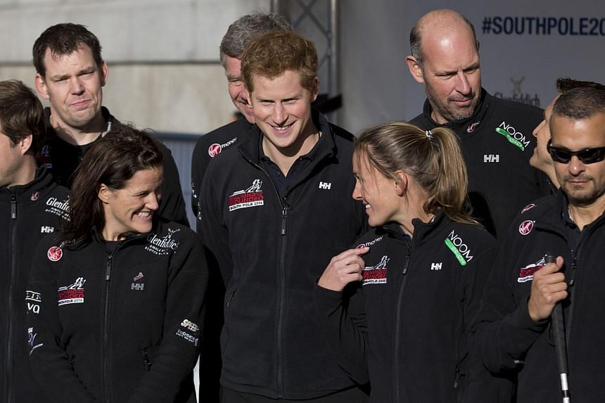 Britain's Prince Harry, center, poses for a group photograph on stage with other people who will take part in the Walking With The Wounded South Pole Allied Challenge during its departure event in Trafalgar Square, London, on Thursday, Nov 14, 2013.