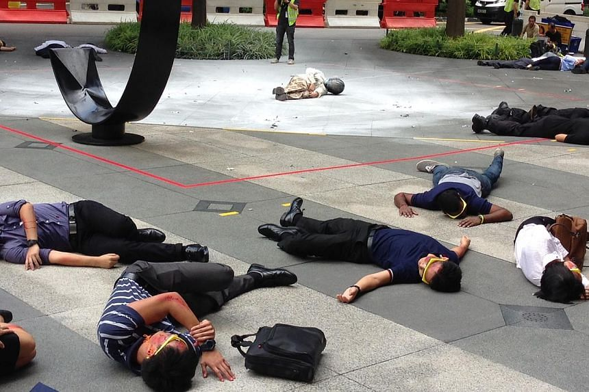 """The aftermath of a """"suicide bomber attack"""" in front of the Singapore Land Tower in Raffles Place, one of the scenarios in Exercise Heartbeat.-- ST PHOTO: YEO SAM JO"""