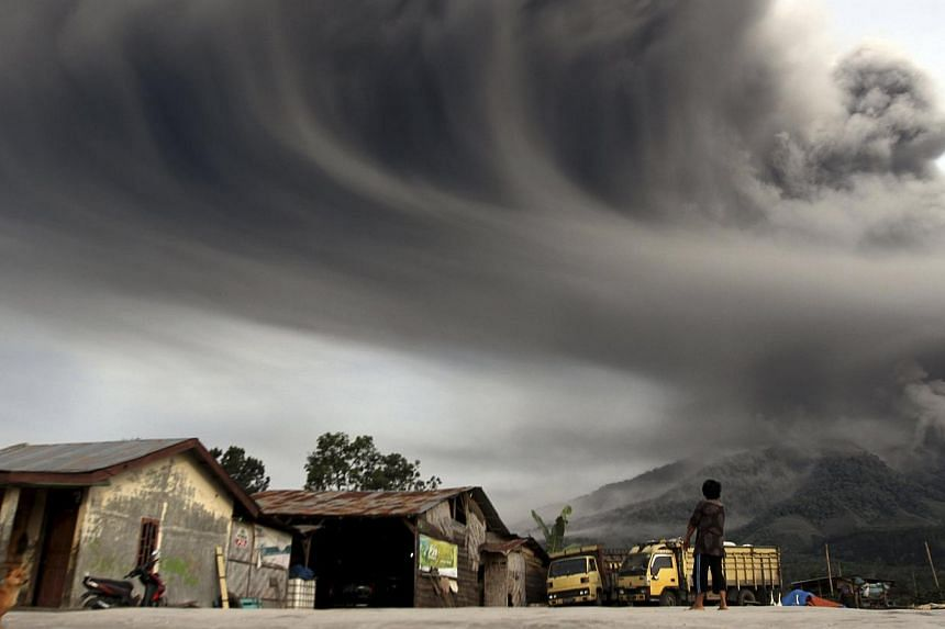 A woman looks on as Mount Sinabung spews ash, as pictured from Sibintun village in Karo district, Indonesia's north Sumatra province November 18, 2013. Mount Sinabung continued to spew volcanic ash throwing a plume 8,000 meters into the atmosphere on