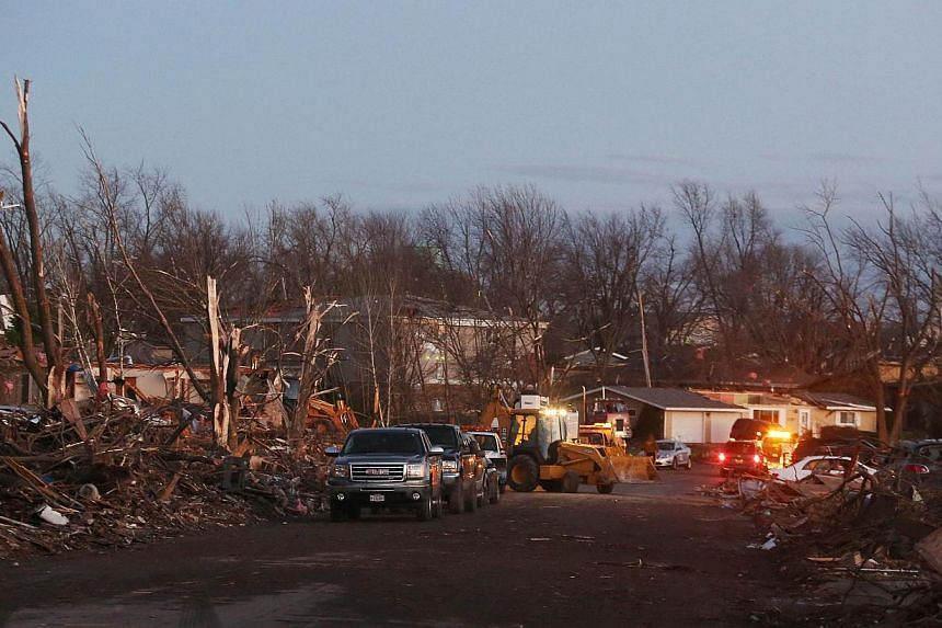 The damage is surveyed along Elgin Avenue after a tornado struck on Nov 17, 2013, in Washington, Illinois. At least five people were killed and dozens more hurt as severe storms and violent tornadoes battered the US Midwest on Sunday, and officials w
