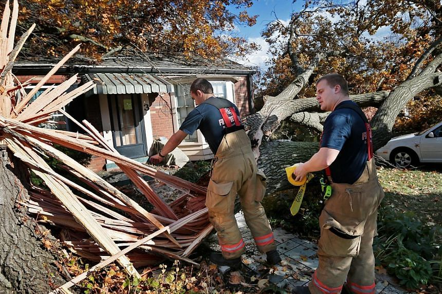 Webster Groves firefighters Chris Manita (centre) and Matt Grossenhieder climb over a tree that fell on a house on Clydehurst Drive in Webster Groves, Missouri onSunday, Nov 17, 2013. A fast-moving storm system that produced at least one tornad