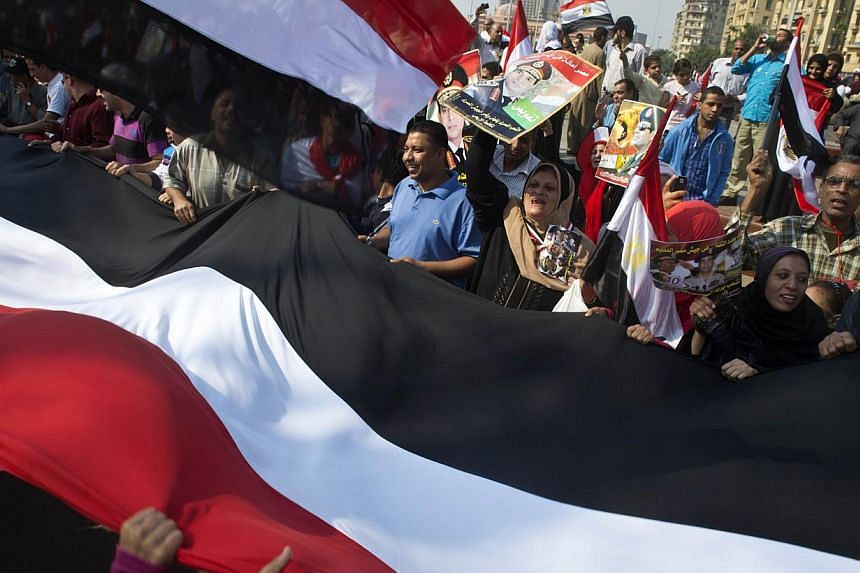 Egyptians wave a giant national flag on Tahrir Square as they mark the 40th anniversary of the 1973 Arab-Israeli war on Oct 6, 2013 in the Egyptian capital Cairo.Hundreds of Egyptians gathered in Cairo's Tahrir Square Monday to mark the anniver