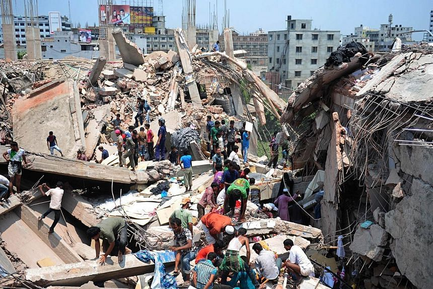 This file photo taken on april 24, 2013 shows Bangladeshi civiliant volunteers assisting in rescue operations after an eight-storey building collapsed in Savar, on the outskirts of Dhaka.Bangladesh must improve conditions in its garment i