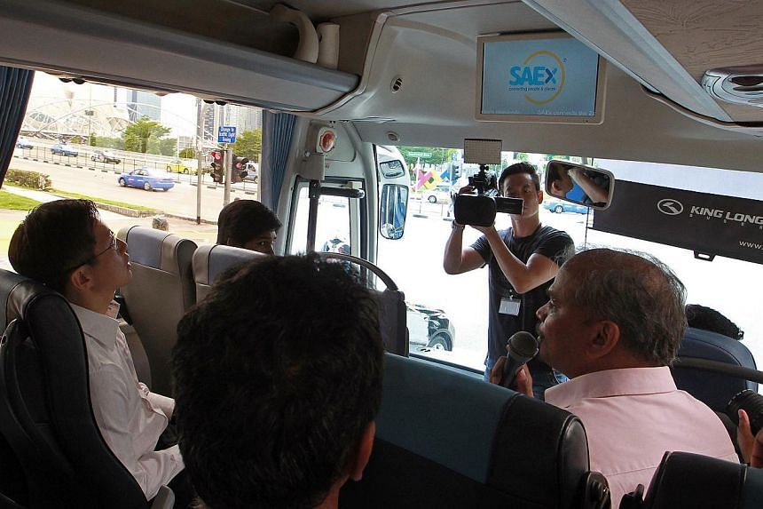 Minister of State for Trade & Industry Mr Teo Ser Luck (extreme left), looks at the television screen that indicates the upcoming nearby destination as the details of the location are played over the sound system, during the maiden bus tour of th