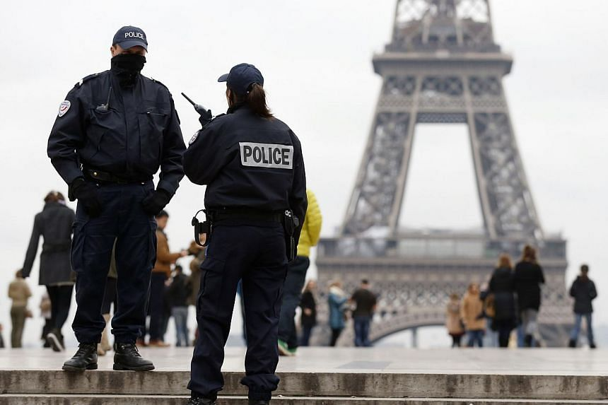 Police officers patrol at the Trocadero Esplanade (also named Human rights Esplanade) in front of the Eiffel Tower on Nov 18, 2013 in Paris, while a frantic manhunt is underway after a 27-year-old fought for his life after being shot at the Paris off