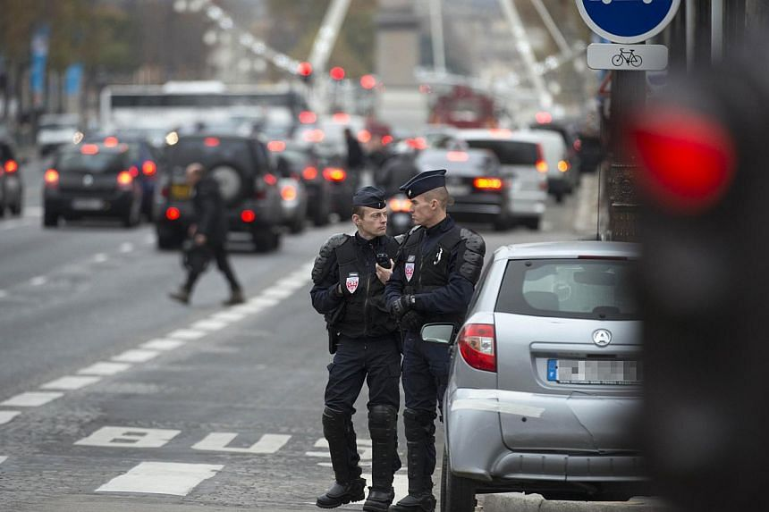 Police officers patrol on the Champs-Elysees avenue on Nov 18, 2013 in Paris as a frantic manhunt is underway after a 27-year-old fought for his life after being shot at the Paris offices of French daily Liberation and the shooter fled the scene. &nb
