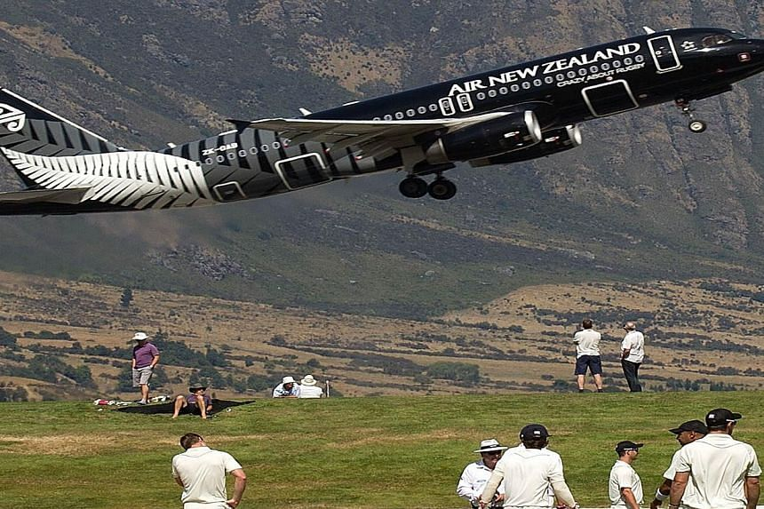 A file photo taken on Feb 27, 2013 shows an Air New Zealand jet taking off above the cricketers during an International cricket match between a New Zealand XI and England played in Queenstown. The New Zealand government said on Tuesday it has sold a
