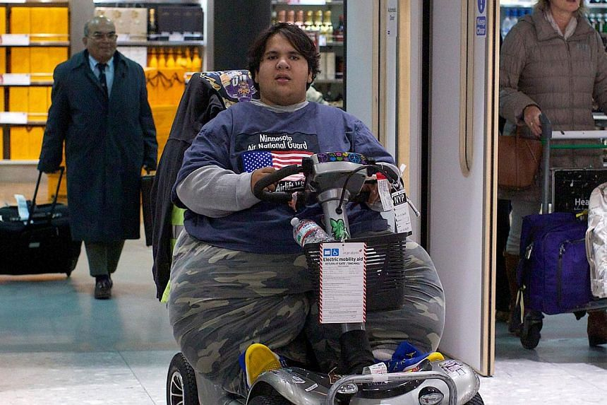 French Kevin Chenais, who was deemed too fat to fly, exits Heathrow Airport upon arrival on a plane from New York to London, on Nov 19, 2013. A young Frenchman who was stranded in the United States because he was deemed too heavy to fly finally took