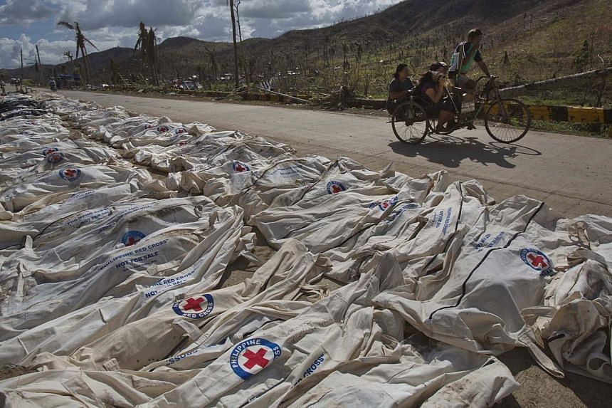 Typhoon Haiyan survivors pass by hundreds of victims lying in body bags on the roadside until forensic experts can register and bury them in a mass grave outside of Tacloban, Philippines, on Tuesday, Nov 19, 2013. Interpol said on Tuesday that it had