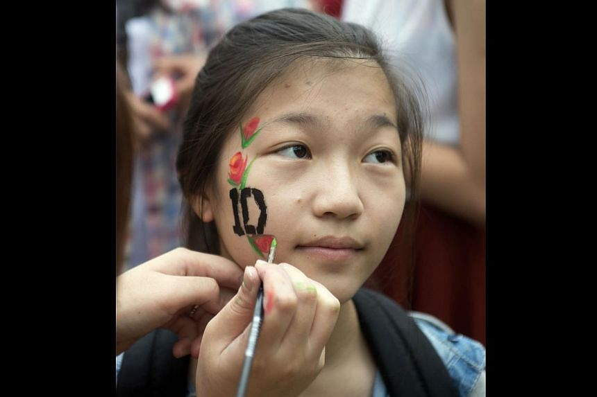 """A fan getting the """"1D"""", which stands for One Direction, painted on her face at one of the booths."""