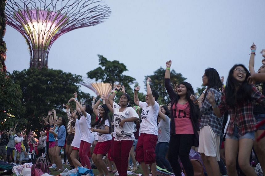 One Direction enthusiasts at the Supertree Grove in Gardens by the Bay to film a mass dance (above) that will be part of video footage that will be broadcast through global streaming. -- ST PHOTO: CHERYL FAITH WEE
