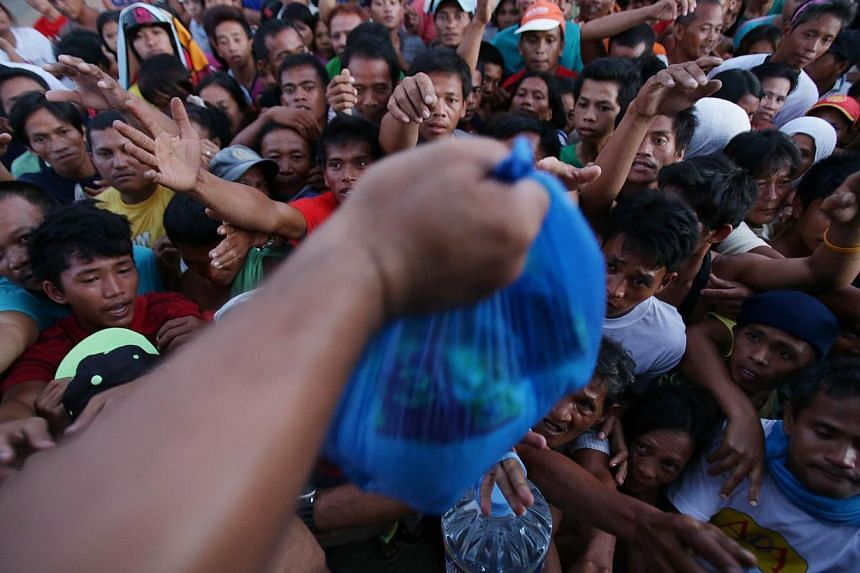 Survivors struggle to receive relief goods from a private group in typhoon hit Tacloban, Leyte province, central Philippines Monday, Nov. 18, 2013. -- PHOTO: AP