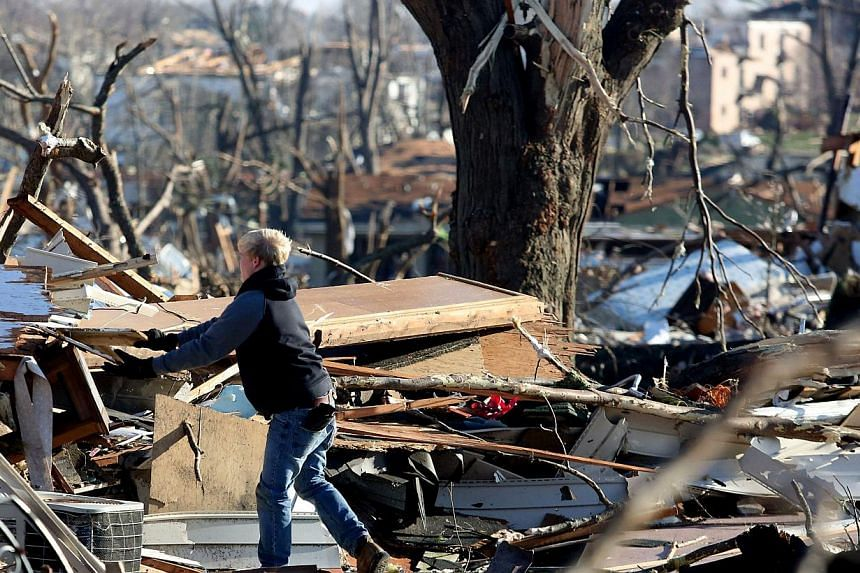 A person sorts the damage of a home in the Washington Estates sudivision in the aftermath of a tornado on Nov 18, 2013 in Washington, Illinois. A fast-moving storm system that produced several tornadoes that touched down across the Midwest left