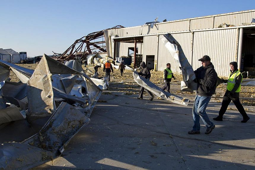 Employees of Voestalpine Rotec Inc. help clean the lot after the building was heavily damaged after Sunday's storms Monday, Nov 18, 2013, in Lafayette, Indiana. Dozens of tornadoes and intense thunderstorms swept across the US Midwest on Sunday, unle