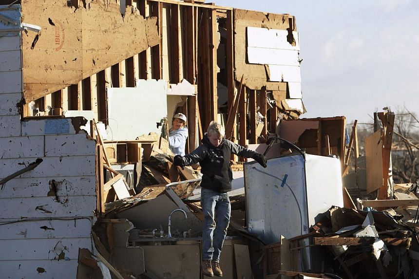 A resident jumps between debris while looking through a home in Washington, Illinois, on Monday, Nov 18, 2013, that was destroyed by a tornado the day before in this central Illinois town. The unusually powerful late-season wave of thunderstorms brou