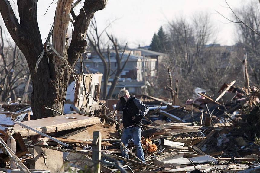 A resident searches through the debris of a home in Washington, Illinois, on Monday, Nov 18, 2013, that was destroyed by a tornado the day before in this central Illinois town. The unusually powerful late-season wave of thunderstorms brought damaging