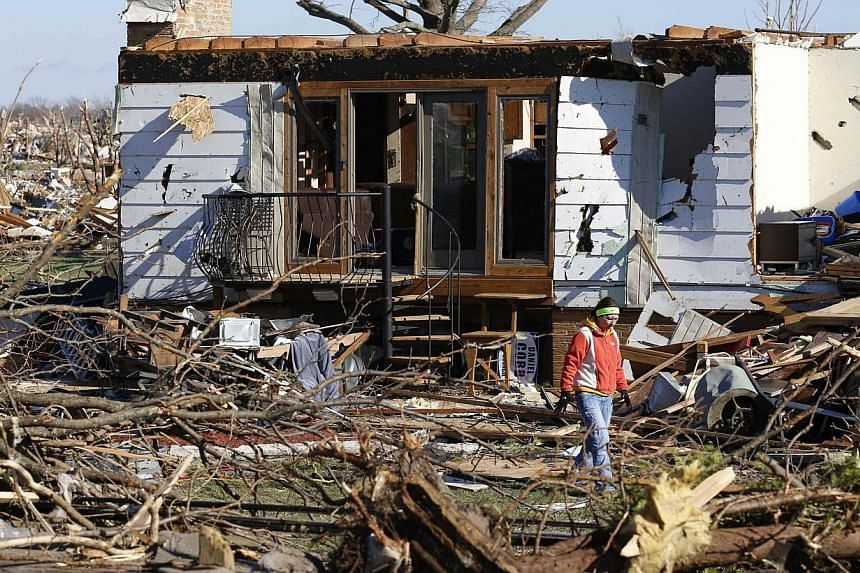A woman walks through the debris from the destruction caused by a tornado that touched down in Washington, Illinois, on Nov 18, 2013. A fast-moving storm system triggered multiple tornadoes on Sunday that killed at least six people and flattened larg