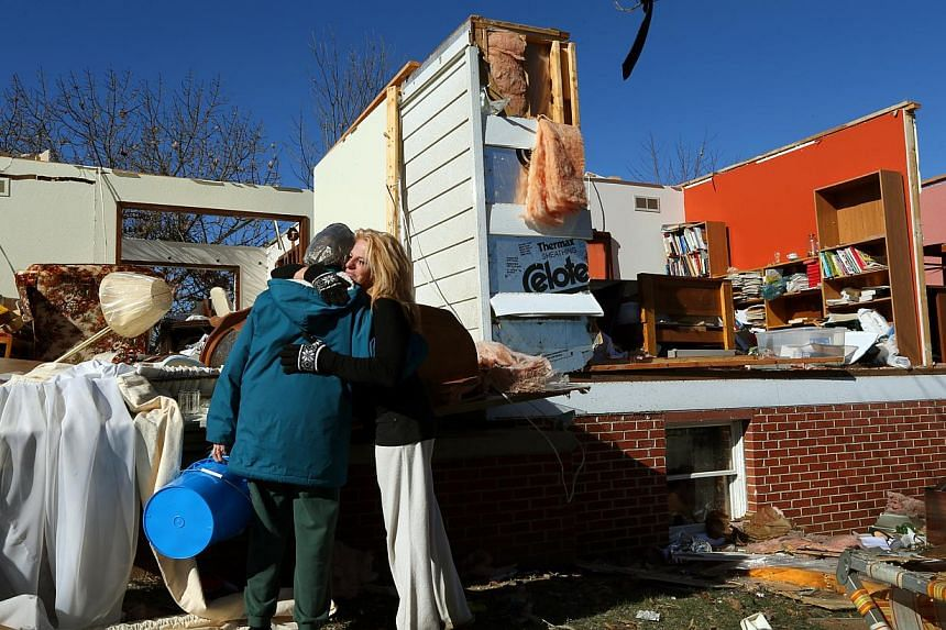 Ms Rochelle Scott, right, hugs Ms Eunice Hausler while helping her recover her belongings in New Minden, Illinois, on Monday, Nov 18, 2013. Dozens of tornadoes and intense thunderstorms swept across the US Midwest on Sunday, unleashing powerful winds