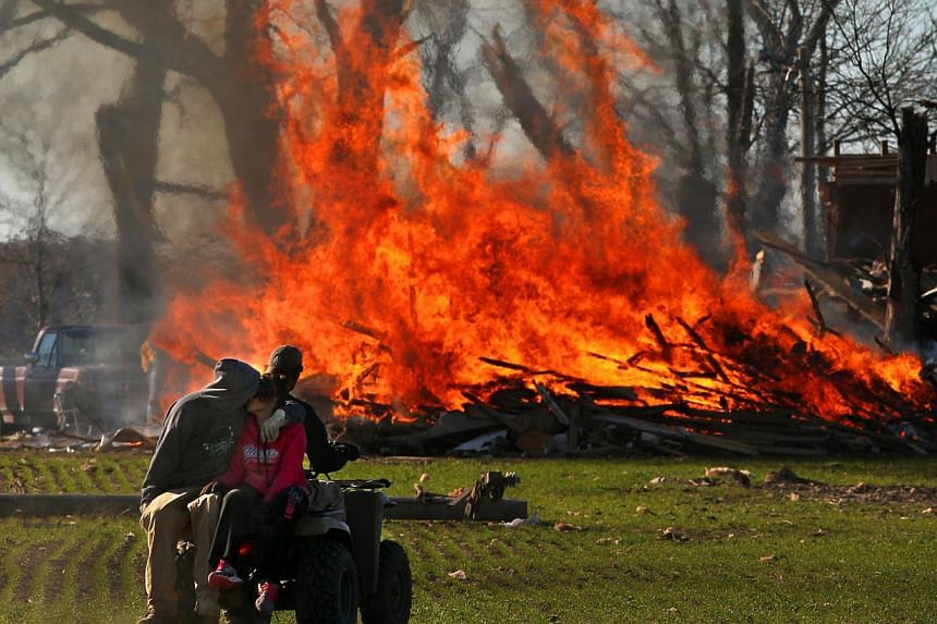 Residents burn storm debris from a home destroyed in Sunday's tornado on Monday, Nov 18, 2013. Dozens of tornadoes and intense thunderstorms swept across the US Midwest on Sunday, unleashing powerful winds that flattened entire neighborhoods, flipped
