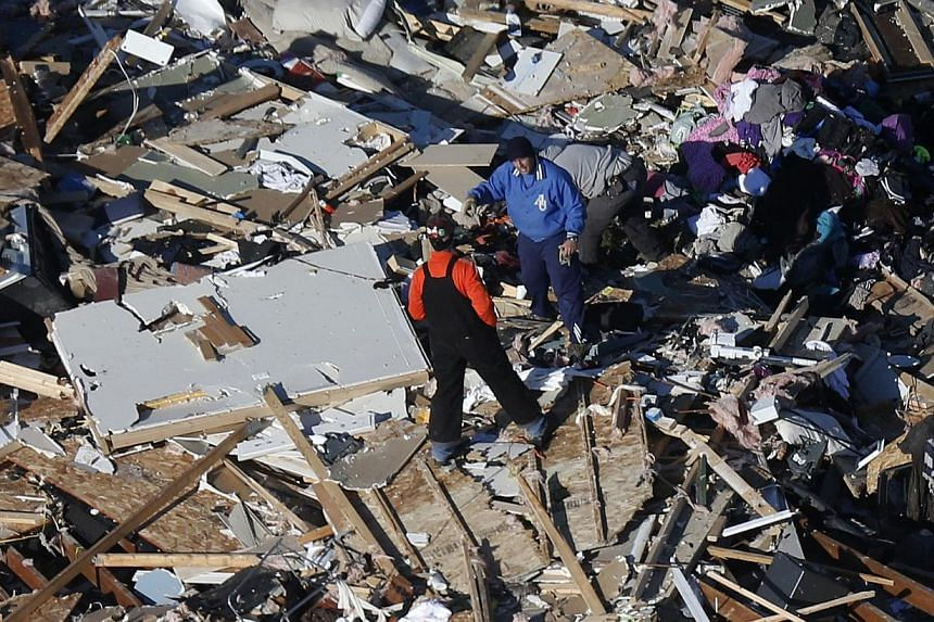 This aerial view on Monday, Nov 18, 2013, two men walk through what is left of a home that was destroyed by a tornado that hit the western Illinois town of Washington on Sunday. It was one of the worst-hit areas after intense storms and tornadoes swe
