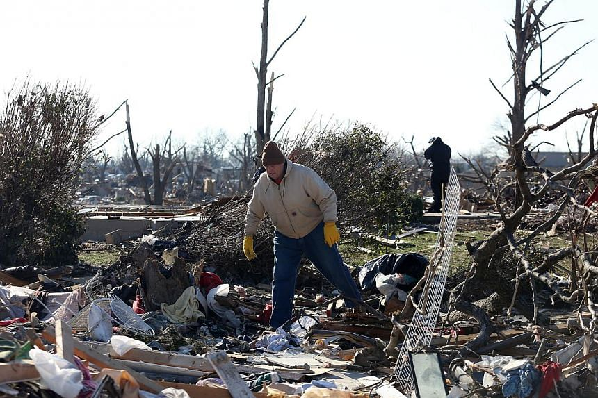 A person looks at the damage of a home in the Washington Estates sudivision in the aftermath of a tornado on Nov 18, 2013 in Washington, Illinois. A fast-moving storm system that produced several tornadoes that touched down across the Midwest left be