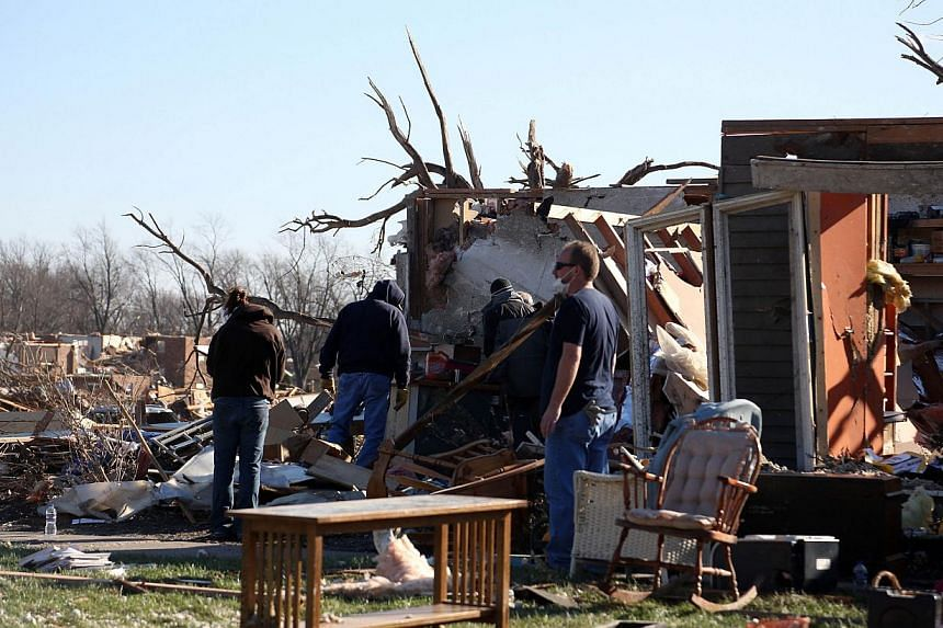 People survey the damage in the Washington Estates sudivision in the aftermath of a tornado on Nov 18, 2013 in Washington, Illinois. A fast-moving storm system that produced several tornadoes that touched down across the Midwest left behind a path of