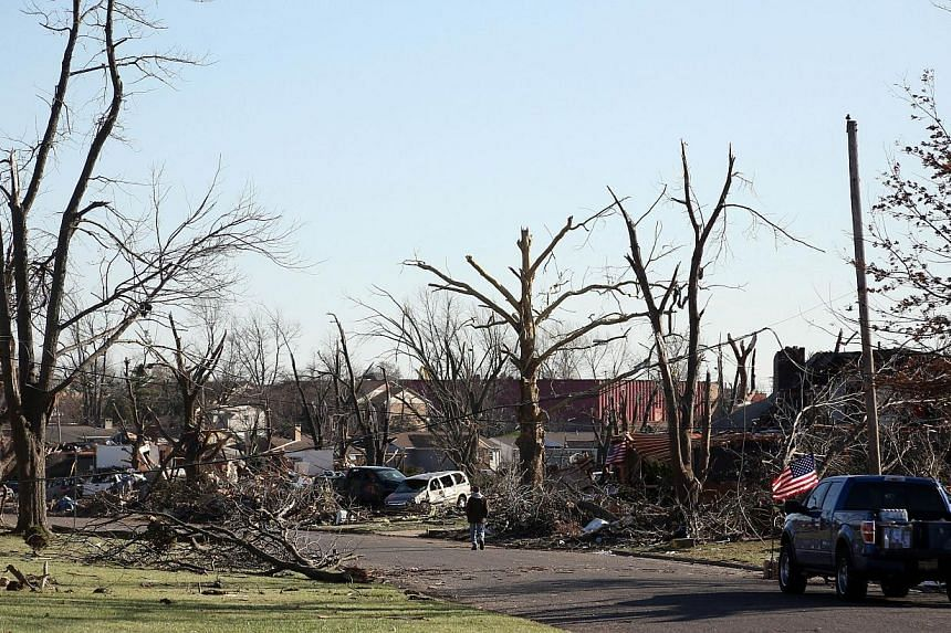 A person walks down the street amongst the damage in the Washington Estates sudivision in the aftermath of a tornado on Nov 18, 2013 in Washington, Illinois. A fast-moving storm system that produced several tornadoes that touched down across the Midw