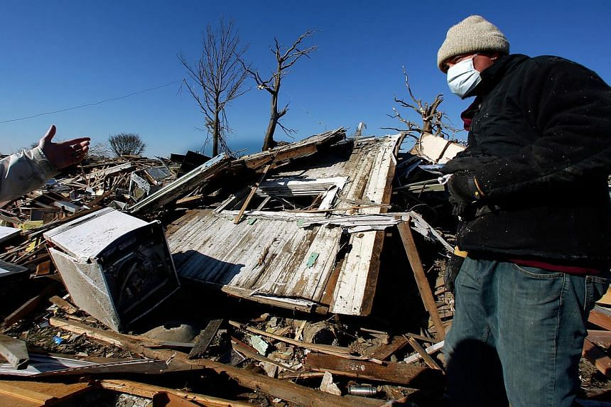 Ben DuBois tries to salvage what he can from his home the day after a tornado destroyed his house on Monday, Nov 18, 2013, in Washington Illinois. The tornado that hit the western Illinois town of Washington on Sunday was one of the worst-hit areas a
