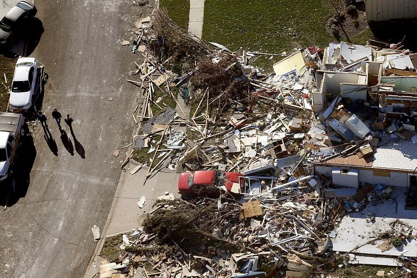 This aerial view on Monday, Nov 18, 2013, shows three people walking down a street where homes were destroyed by a tornado that hit the western Illinois town of Washington on Sunday. It was one of the worst-hit areas after intense storms and tornadoe