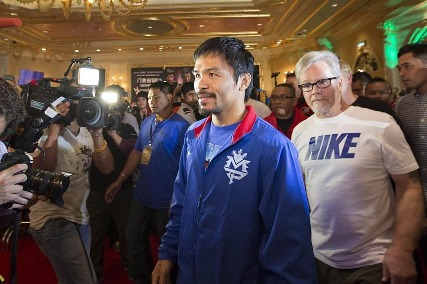 This handout photo taken on Tuesday, Nov 19, 2013, and received by Sands China Ltd on Wednesday, Nov 20, 2013, shows boxer Manny Pacquiao (centre) of the Philippines and his trainer Freddie Roach (second from right) arriving at the main lobby of the