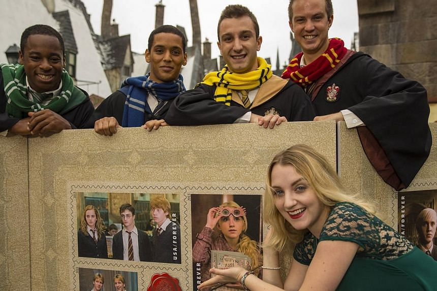 Evanna Lynch (Right), who played Luna Lovegood in the Harry Potter films, poses with people dressed as Hogwarts students to unveil the USPS Harry Potter Limited-Edition Forever stamp collection at the Universal Orlando Resort in Orlando Nov 19, 2013.