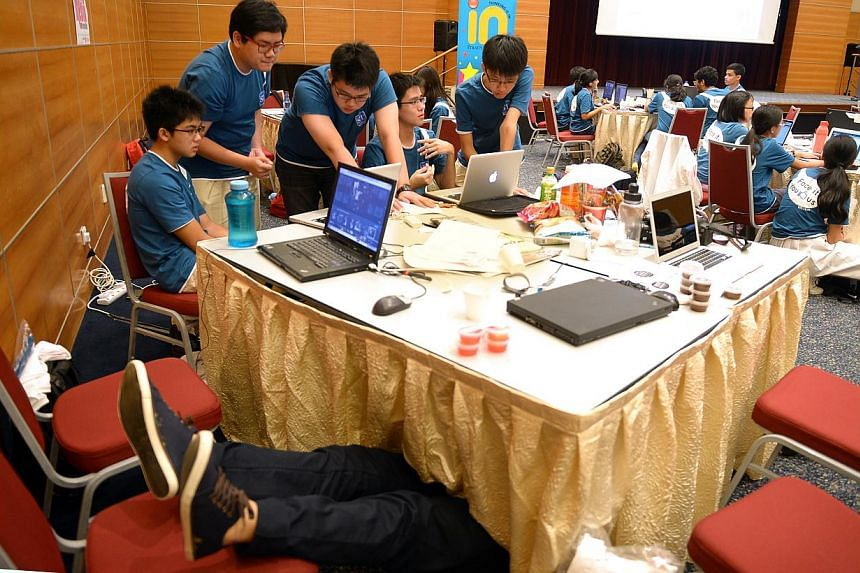 (From left) Hwa Chong Institution students Ian Wong (legs showing), Danyon Low, Denis Lan, Gaw Ban Siang, Brandon Hoong and Joel Lim. Ian Wong dived under his team's workbench for a short nap during The Straits Times National Youth Media Competition,