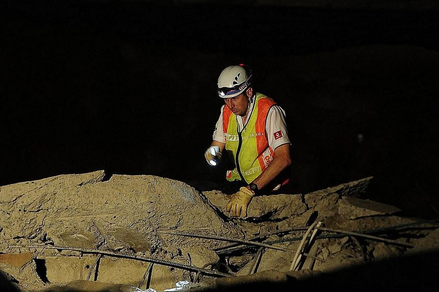 A paramedic looks for people trapped in a mall that collapsed inTongaat, South Africa, on Tuesday, Nov 19, 2013.-- PHOTO: AP