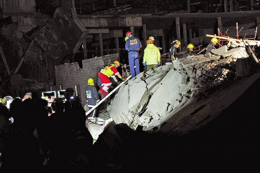 Paramedics look for people trapped in a mall that collapsedinTongaat, South Africa, on Tuesday, Nov 19, 2013.-- PHOTO: AP