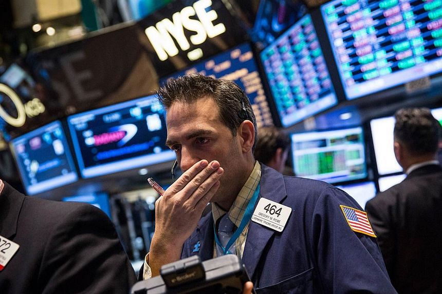A trader works on the floor of the New York Stock Exchange during morning trading Nov 15, 2013 in New York City. US stocks fell modestly on Tuesday, ending the Dow's four-day streak of fresh records, as the Justice Department announced a record US$13