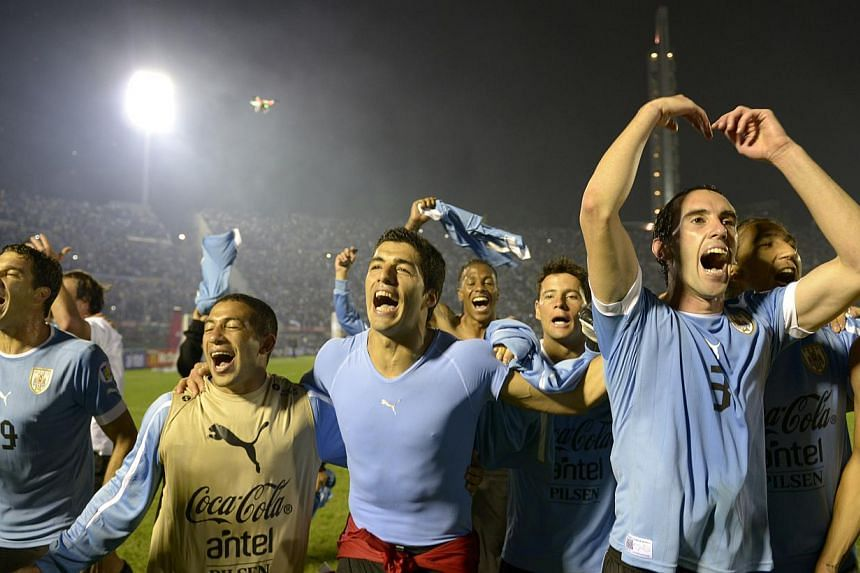 Uruguay's players (from left) Andres Scotti, Walter Gargano, Luis Suarez and Diego Godin celebrate after qualifying for the 2014 World Cup after playing a World Cup qualifying play-off second leg soccer match against Jordan in Montevideo, Uruguay, on
