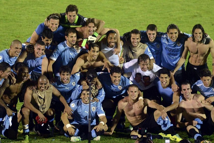 Uruguay's players celebrate at the end of their 2014 World Cup qualifying play-off second leg soccer match against Jordan in Montevideo on Nov 20, 2013.  -- PHOTO : REUTERS