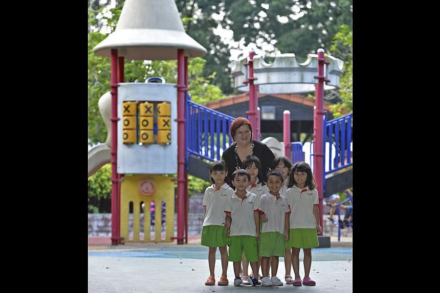 Ms Tan Bee Geok with some of her little charges at PCF Little Wings Jurong Spring Childcare Centre. Ms Tan was a cook at a childcare centre before she went back to school at the age of 45 to get the necessary qualifications to be a pre-school teacher
