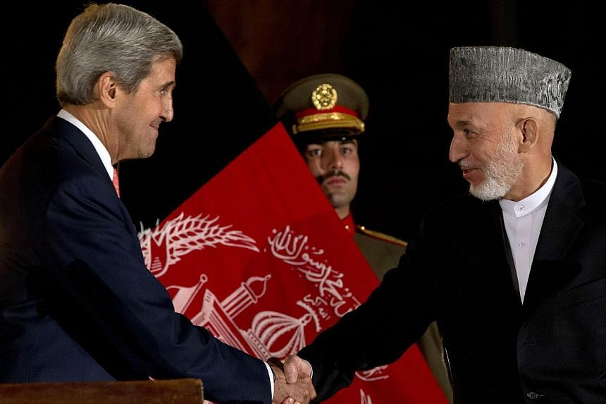 Afghanistan's President Hamid Karzai (right) shakes hands with United States (US) Secretary of State John Kerry after a news conference at the Presidential Palace in Kabul in this Oct 12, 2013, file photo. Mr Kerry said on Nov 20 that he had nailed d