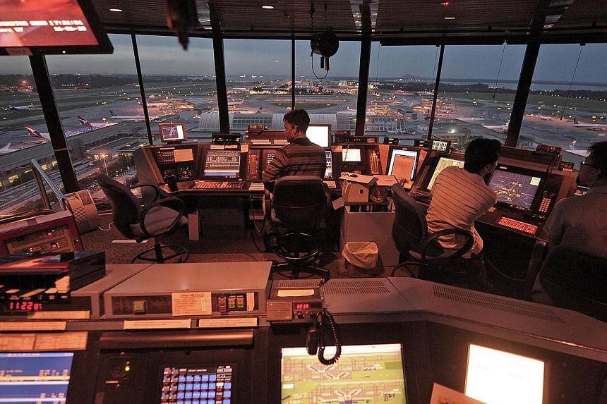 Air traffic controllers work inside the iconic Changi Airport control tower. Changi Airport handled 4.41 million passengers in October, a 3.2 per cent jump from the same month a year ago. -- ST FILE PHOTO: DESMOND LIM