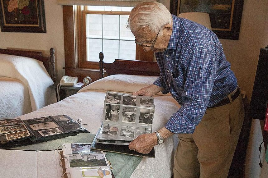 John Betar looks through old photo albums at his home in Fairfield, Connecticut, on Nov 20, 2013. -- PHOTO: REUTERS