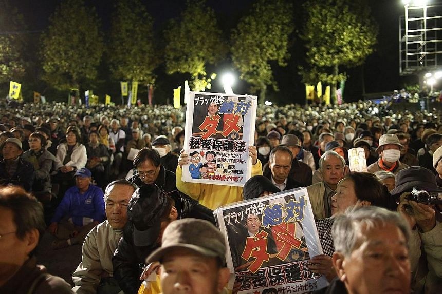 Protesters hold placards with a photo of Japan's Prime Minister Shinzo Abe, during a rally against the government's planned secrecy law in Tokyo, on Nov 21, 2013. -- PHOTO: REUTERS