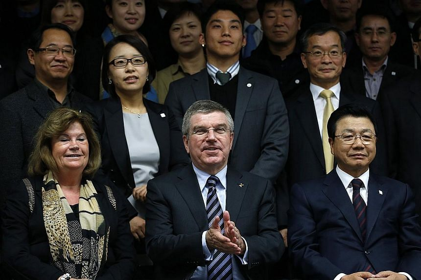 International Olympic Committee (IOC) President Thomas Bach (bottom centre) takes a group photo with members of the PyeongChang Organizing Committee for the 2018 Olympic and Paralympic Winter Games (POCOG) after a news conference in Seoul, on Nov 21,