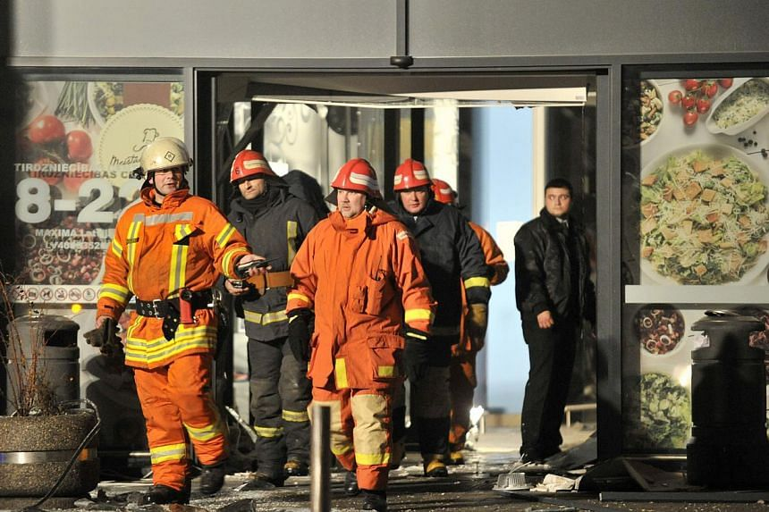 Rescuers work at the Maxima grocery store after its roof collapsed in Riga, Latvia, Nov 21, 2013. Rescue services said on Friday that 12 people had died after the roof of a supermarket collapsed in the capital, Riga, the previous day. -- PHOTO: AP