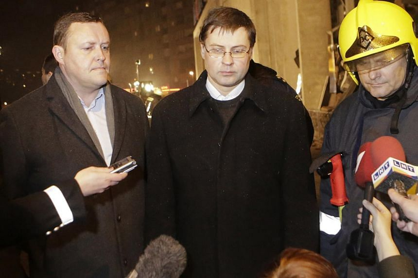 Latvia's Interior Minister Rihards Kozlovskis (left), Prime Minister Valdis Dombrovskis (centre) and a senior emergency services official speak to the media near the collapsed Maxima supermarket in Riga, Nov 21, 2013. Rescue services said on Friday t